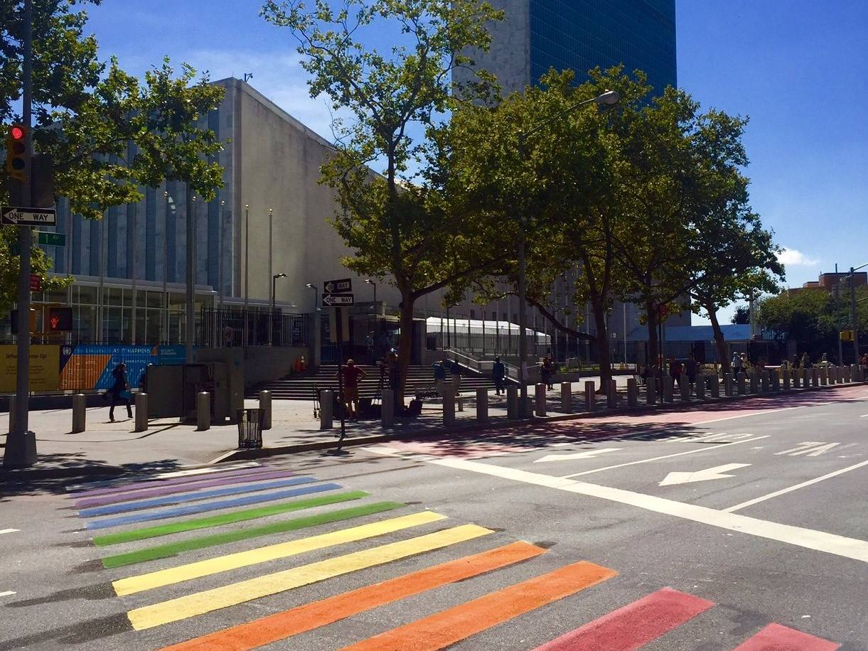 Pedestrian crossing outside the UN painted in the colours of the rainbow flag - mynd